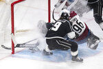 Los Angeles Kings goaltender Calvin Petersen, left, dives to stop the puck rolling behind him during the second period of the team's NHL hockey game against the Colorado Avalanche on Tuesday, Jan. 19, 2021, in Los Angeles. (AP Photo/Kyusung Gong)