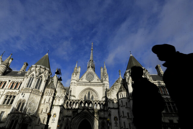 Pedestrian pass by The Royal Courts Of Justice, in London, Tuesday, Jan. 19, 2021. Meghan, the Duchess of Sussex will ask a High Court judge to rule in her favour in her privacy action against the Mail on Sunday over the publication of a handwritten letter to her estranged father. The case will be heard remotely due to the pandemic. (AP Photo/Kirsty Wigglesworth)