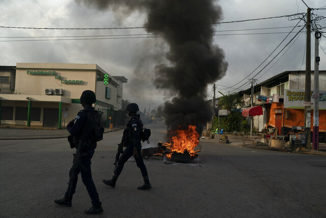 Policemen walk past a burning barricade during a protest after the security forces blocked the access to the house of the former president Henri Konan Bedie, in Abidjan, Ivory Coast, Tuesday, Nov. 3, 2020. Ivory Coast's electoral commission said Tuesday that President Alassane Ouattara had overwhelmingly won a third term in office after his two main opponents boycotted the election and called his candidacy illegal. (AP Photo/Leo Correa)