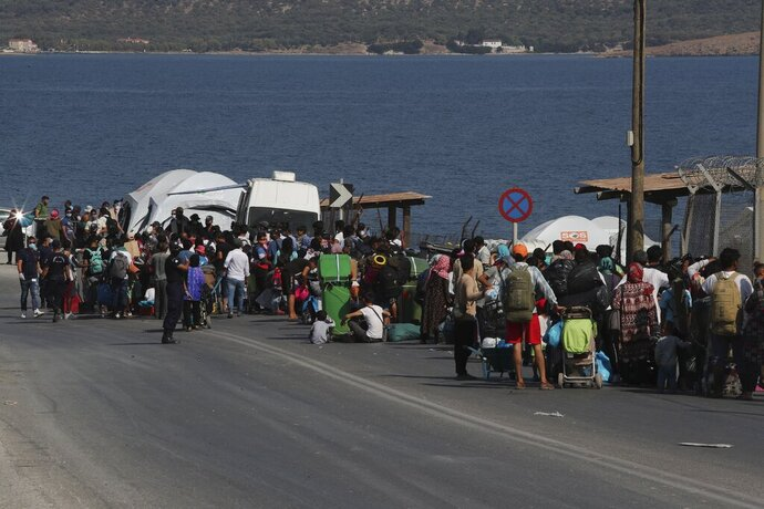 Migrants wait to enter a new temporary refugee camp in Kara Tepe, near Mytilene the capital of the northeastern island of Lesbos, Greece, Thursday, Sept. 17, 2020. Greek police are moving hundreds of migrants to an army-built camp on the island of Lesbos Thursday after a fire destroyed an overcrowded facility, leaving them homeless for days. (AP Photo/Petros Giannakouris)