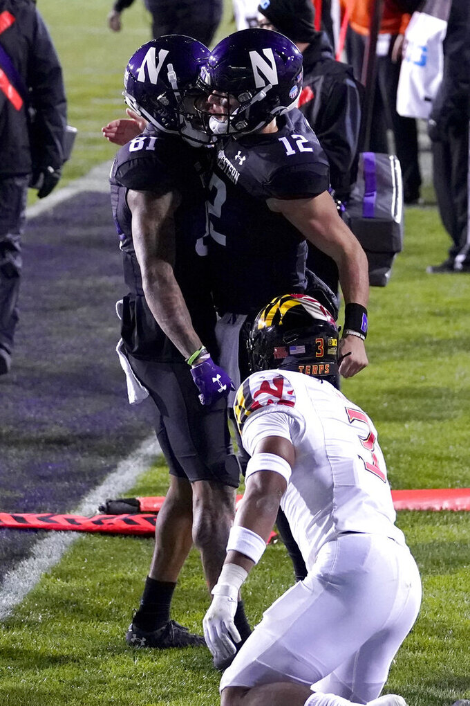 Northwestern quarterback Peyton Ramsey (12) celebrates with wide receiver Ramaud Chiaokhiao-Bowman (81) after scoring a touchdown as Maryland defensive back Nick Cross (3) looks on during the first half of an NCAA college football game in Evanston, Ill., Saturday, Oct. 24, 2020. (AP Photo/Nam Y. Huh)