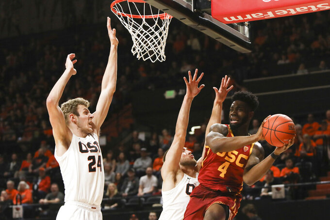 Southern California's Daniel Utomi (4) passes away from the basket to avoid Oregon State's Kylor Kelley (24) and Tres Tinkle (3) during the first half of an NCAA college basketball game in Corvallis, Ore., Saturday, Jan. 25, 2020. (AP Photo/Amanda Loman)