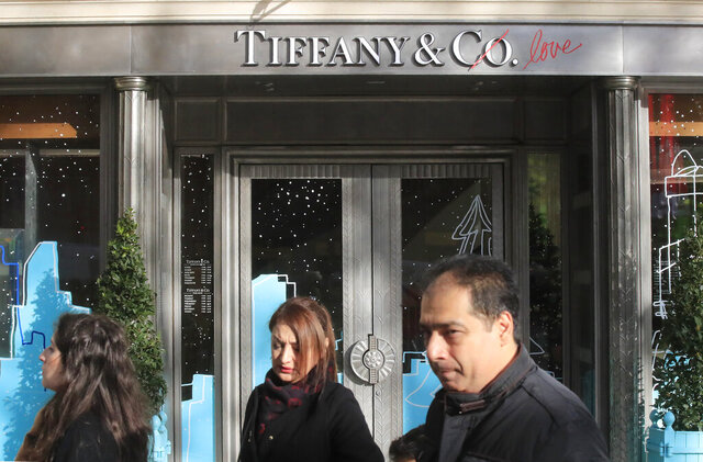 FILE - In this Nov. 25, 2019 file photo, people walk past a Tiffany jeweler shop on the Champs Elysees avenue in Paris. LVMH and Tiffany have worked through their differences, with the famous jewelry company agreeing to be purchased by the luxury goods company for slightly less than what they initially agreed on. (AP Photo/Michel Euler, File)