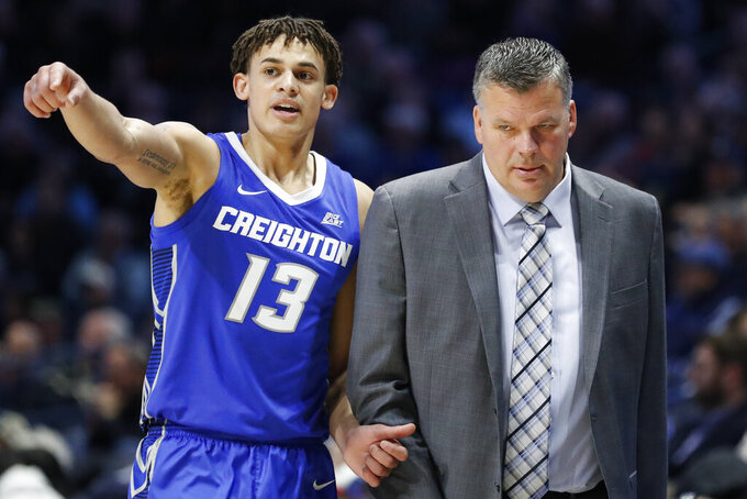 Creighton coach Greg McDermott, right, speaks with Christian Bishop during the first half of the team's NCAA college basketball game against Xavier, Wednesday, Feb. 13, 2019, in Cincinnati. (AP Photo/John Minchillo)