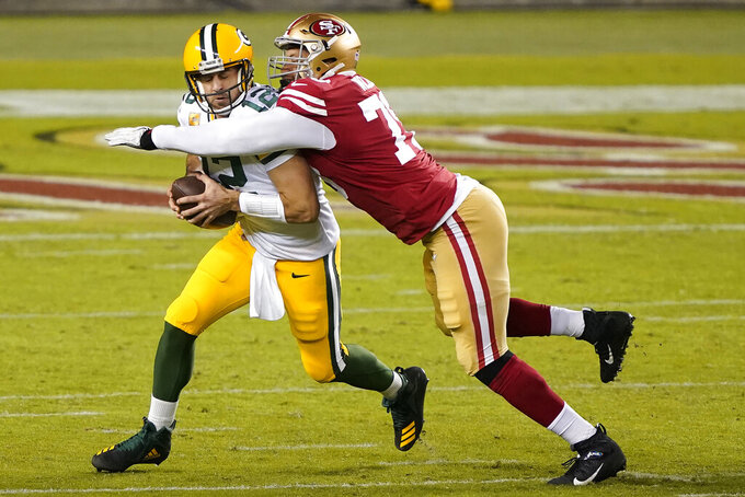 Green Bay Packers quarterback Aaron Rodgers, left, is sacked by San Francisco 49ers defensive lineman Jordan Willis during the first half of an NFL football game in Santa Clara, Calif., Thursday, Nov. 5, 2020. (AP Photo/Tony Avelar)