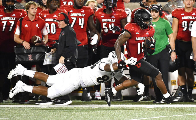 Central Florida defensive lineman Josh Celiscar (88) attempts to bring down Louisville running back Jalen Mitchell (15) during the first half of an NCAA college football game in Louisville, Ky., Friday, Sept. 17, 2021. (AP Photo/Timothy D. Easley)