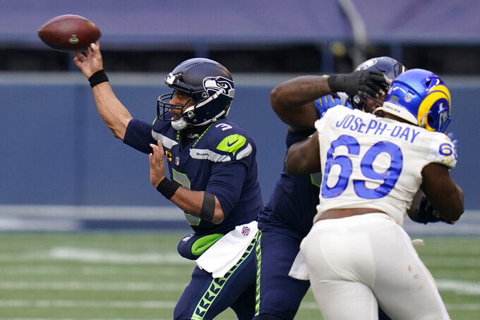 Seattle Seahawks quarterback Russell Wilson (3), left, passes against the Los Angeles Rams during the first half of an NFL football game, Sunday, Dec. 27, 2020, in Seattle. (AP Photo/Elaine Thompson)