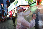 Artists perform under a billboard displaying information on COVID-19 in a sparsely populated Times Square, Friday, March 20, 2020, in New York. New York Gov. Andrew Cuomo is ordering all workers in non-essential businesses to stay home and banning gatherings statewide.