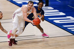 Loyola Chicago center Cameron Krutwig, left, looks to pass in front of Georgia Tech forward Khalid Moore in the first half of a college basketball game in the first round of the NCAA tournament at Hinkle Fieldhouse, Indianapolis, Friday, March 19, 2021. (AP Photo/AJ Mast)