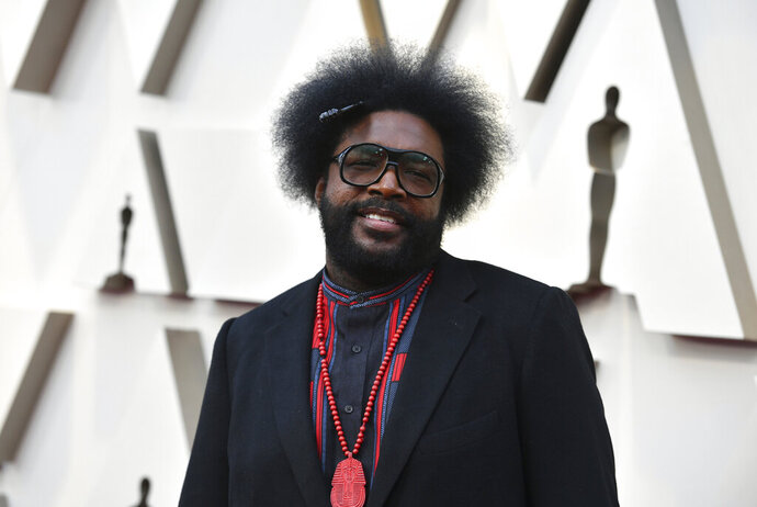 """Questlove arrives at the Oscars on Sunday, Feb. 24, 2019, at the Dolby Theatre in Los Angeles. The founder of the hip-hop group The Roots wants to find the woman who bought a turntable and records for him when he was 5. He posted about his quest on social media over the weekend. He wrote that he was in Portland, Maine, in 1976 when he made friends with a stranger. He said he knew talking to strangers was a no-no but says """"my instincts paid off."""" Now he's hoping to find Ellie. (Photo by Jordan Strauss/Invision/AP)"""