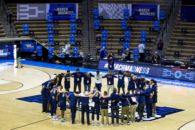 Oral Roberts players and coaches form a prayer circle on the court following their win over Ohio State in a first-round game in the NCAA men's college basketball tournament, Friday, March 19, 2021, at Mackey Arena in West Lafayette, Ind. (AP Photo/Robert Franklin)