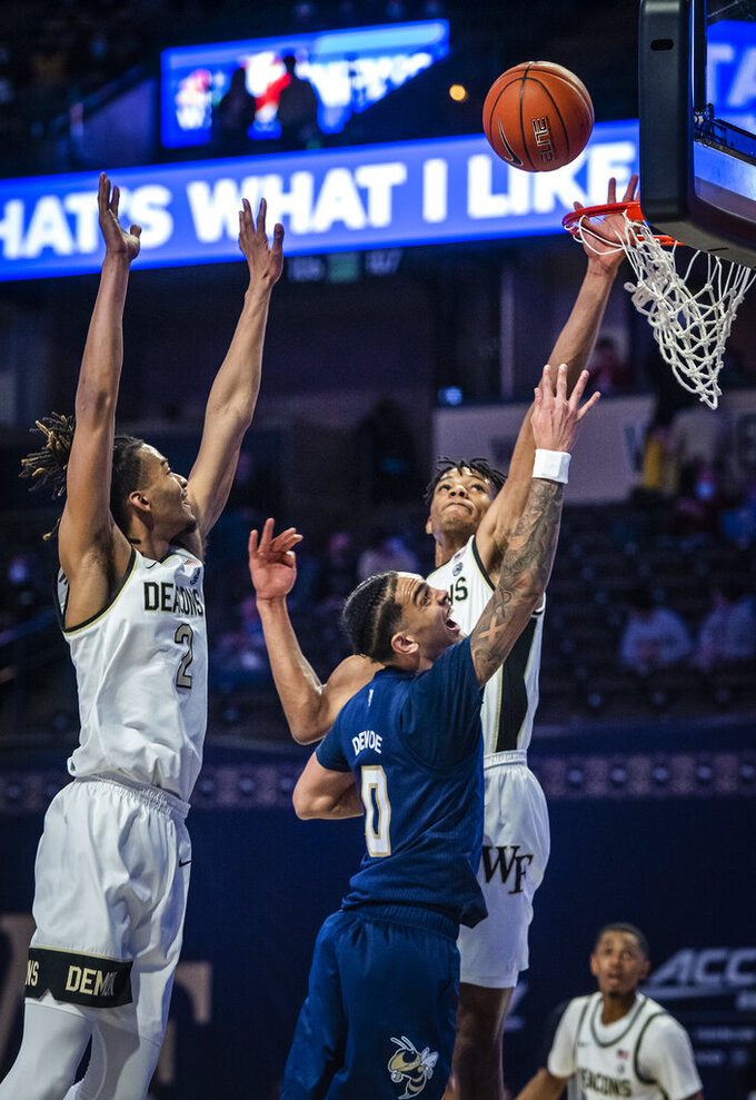 Georgia Tech guard Michael Devoe (0) shoots under defense from Wake Forest forward Ody Oguama, right, during an NCAA college basketball game Friday, March 5, 2021, in Winston-Salem, N.C. (Andrew Dye/The Winston-Salem Journal via AP)