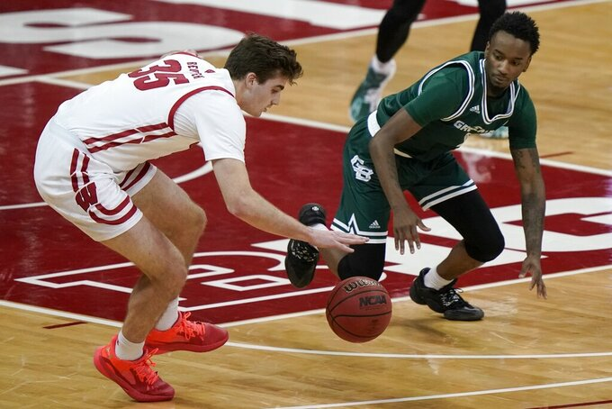 Wisconsin's Nate Reuvers and Wisconsin-Green Bay's Amari Davis go after a lose ball during the first half of an NCAA college basketball game Tuesday, Dec. 1, 2020, in Madison, Wis. (AP Photo/Morry Gash)