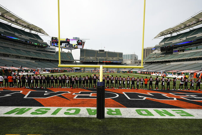 "The Cincinnati Bengals stand arm in arm as ""Lift Every Voice and Sing"" is played before an NFL football game between the Cincinnati Bengals and the Los Angeles Chargers, Sunday, Sept. 13, 2020, in Cincinnati. (AP Photo/Aaron Doster)"