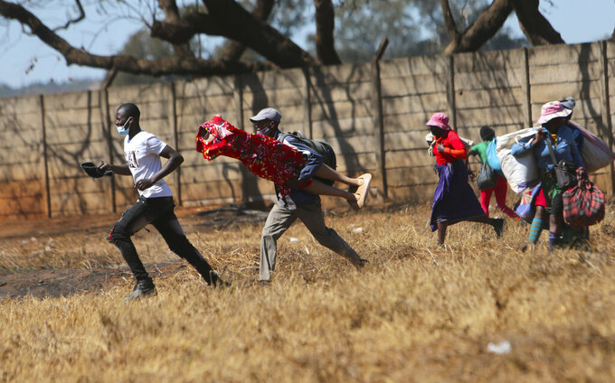 Zimbabwean vendors flee from the police after they were chased away from selling their wares from undesignated areas due to COVID-19 restrictions in Harare, Thursday July 29, 2021.(AP Photo/Tsvangirayi Mukwazhi)