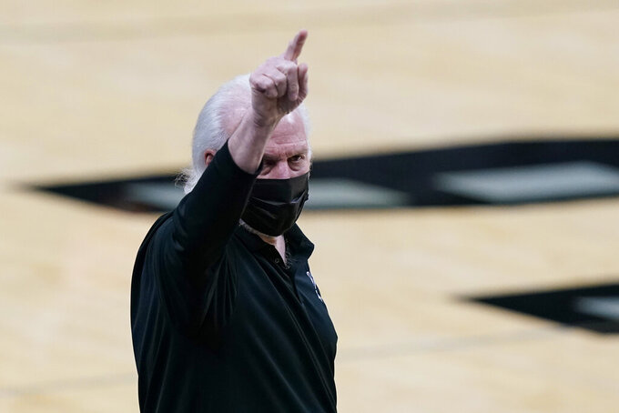 San Antonio Spurs coach Gregg Popovich signals to players during the first half of an NBA basketball game against the Denver Nuggets in San Antonio, Friday, Jan. 29, 2021. (AP Photo/Eric Gay)