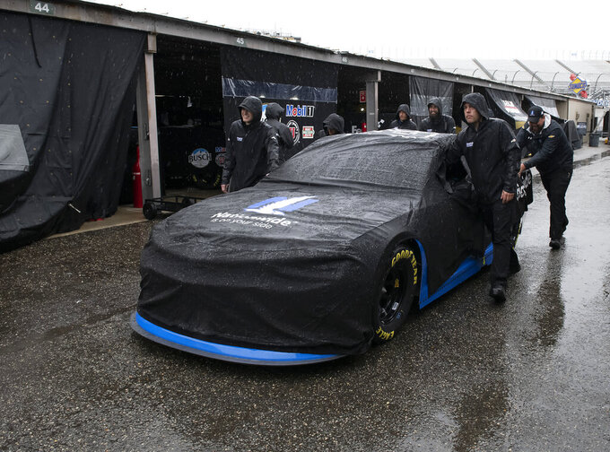 The crew for Alex Bowman No. 88 push their car to the garage as rain falls before a NASCAR Cup series auto race at Dover International Speedway in Dover, Del., Sunday, May 5, 2019. (AP Photo/Jason Minto)