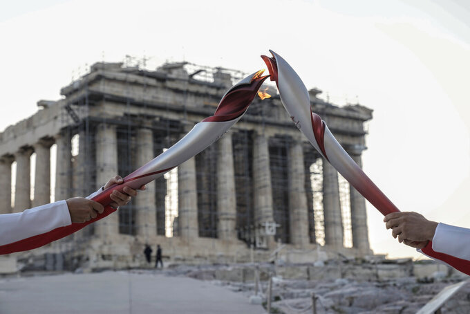 Greek torch bearer Ioannis Melissanidis, left, Olympic gold medalist in Gymnastics , passes the flame to Christos Volikakis, world Champion in Cycling, in front of ancient Parthenon temple atop of the Acropolis Hill in Athens, Tuesday, Oct. 19, 2021. The flame will be transported by torch relay to Beijing, China, which will host the Feb. 4-20, 2022 Winter Olympics.(AP Photo/Petros Giannakouris)