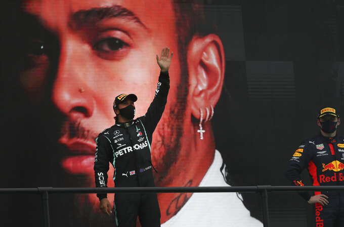 Mercedes driver Lewis Hamilton of Britain, left, waves from the podium after his record breaking win during the Formula One Portuguese Grand Prix at the Algarve International Circuit in Portimao, Portugal, Sunday, Oct. 25, 2020. (Jose Sena Goulao, Pool via AP)