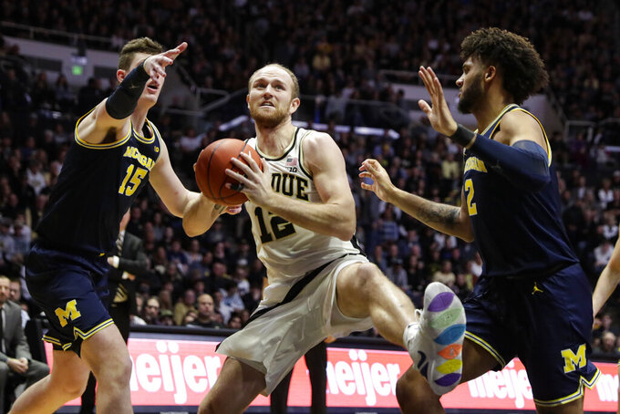 Purdue forward Evan Boudreaux (12) grabs a rebound between Michigan center Jon Teske (15) and forward Isaiah Livers (2) during the second half of an NCAA college basketball game in West Lafayette, Ind., Saturday, Feb. 22, 2020. (AP Photo/Michael Conroy)