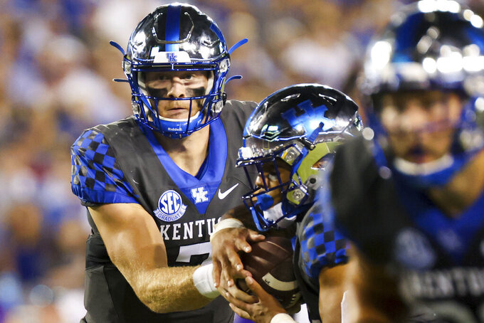 Kentucky quarterback Will Levis (7) hands the ball off during the first half of the team's NCAA college football game against LSU in Lexington, Ky., Saturday, Oct. 9, 2021. (AP Photo/Michael Clubb)