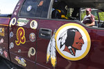 "Rodney Johnson of Chesapeake, Va., stands with his truck outside FedEx Field in Landover, Md., Monday, July 13, 2020. The Washington NFL franchise announced Monday that it will drop the ""Redskins"" name and Indian head logo immediately, bowing to decades of criticism that they are offensive to Native Americans. (AP Photo/Susan Walsh)"