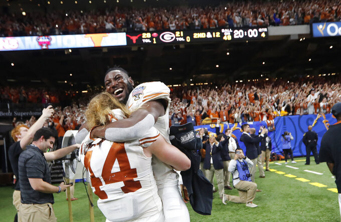 Texas defensive back Kris Boyd (2) hugs defensive lineman Breckyn Hager (44) after Texas defeated Georgia 28-21 in the Sugar Bowl NCAA college football game in New Orleans, Tuesday, Jan. 1, 2019. (AP Photo/Gerald Herbert)