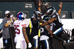 Philadelphia Eagles players celebrate after a touchdown by Boston Scott during the second half of an NFL football game against the New York Giants, Thursday, Oct. 22, 2020, in Philadelphia. (AP Photo/Chris Szagola)