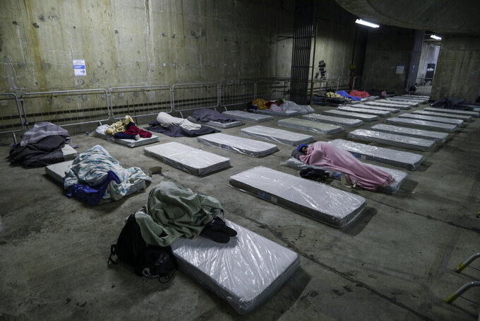Homeless people sleep on mattresses laid out by the government inside a subway station amid historically cold weather in Sao Paulo, Brazil, early Friday, July 30, 2021. The Brazilian government's meteorological institute says low temperatures should endure until the start of August. (AP Photo/Marcelo Chello)