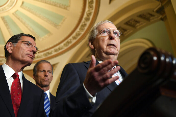 Senate Majority Leader Mitch McConnell of Ky., right, joined by Sen. John Barrasso, R-Wyo., left, and Sen John Thune, R-S.D., center, speaks to reporters following the weekly policy lunches on Capitol Hill in Washington, Tuesday, July 23, 2019. (AP Photo/Susan Walsh)