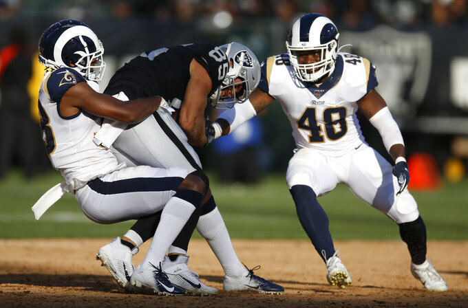 Oakland Raiders' Derek Carrier, center, is tackled by Los Angeles Rams' Mike Thomas, left, and Travin Howard during the first half of a preseason NFL football game Saturday, Aug. 10, 2019, in Oakland, Calif. (AP Photo/D. Ross Cameron)