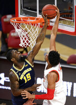 Michigan guard Chaundee Brown (15) blocks a shot byMaryland guard Aaron Wiggins during the first half of an NCAA college basketball game Thursday, Dec. 31, 2020, in College Park, Md. (AP Photo/Nick Wass)