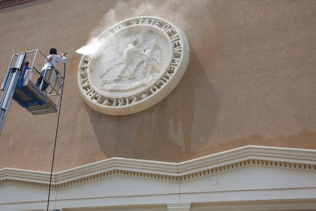 FILE - In this Aug. 24, 2020, file photo, a maintenance worker power-washes the state seal at an entrance of the capitol building in Santa Fe, New Mexico. New Mexico's governor and top health officials are trying to fend off a flurry of lawsuits by business owners who say financial losses caused by the state's pandemic health orders amount to a regulatory taking and should be compensated. (AP Photo/Cedar Attanasio, File)