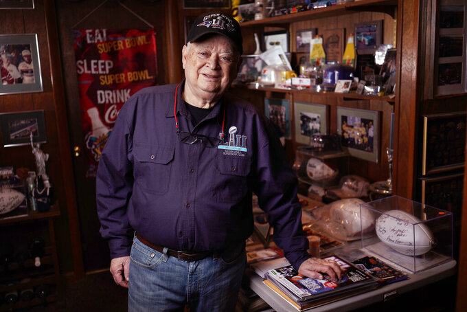 Don Crisman poses for a photo in his Kennebunk, Maine, home on Monday, Jan. 28, 2019, holding a Super Bowl LI ball signed by a few Patriots NFL football players. Crisman has never missed a Super Bowl and will be heading to Atlanta to watch his 53rd Super Bowl as the Patriots take on the Chiefs. (Gregory Rec/Portland Press Herald via AP)