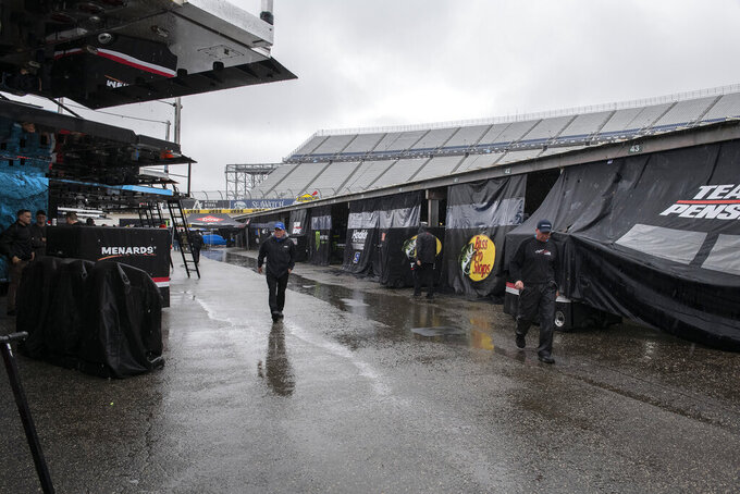 People walk in the garage area as rain falls before a NASCAR Cup series auto race at Dover International Speedway in Dover, Del., Sunday, May 5, 2019. (AP Photo/Jason Minto)