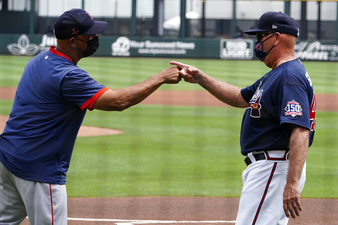 Boston Red Sox manager Alex Cora, left, talks with Atlanta Braves manager Brian Snitker before a spring training baseball game on Monday, March 29, 2021, in North Port, Fla. (AP Photo/John Bazemore)