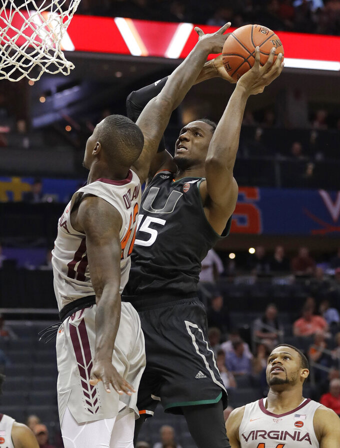 Miami's Ebuka Izundu (15) shoots against Virginia Tech's Ty Outlaw (42) during the second half of an NCAA college basketball game in the Atlantic Coast Conference tournament in Charlotte, N.C., Wednesday, March 13, 2019. (AP Photo/Chuck Burton)