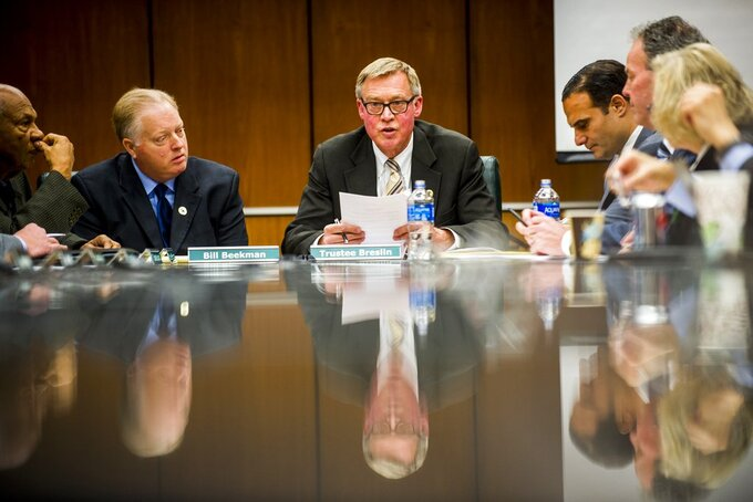 Brian Breslin, center, chairman of the Michigan State board of trustees, announces Bill Beekman as acting president in place of former President Lou Anna Simon during a special Michigan State University board of trustees meeting Friday, Jan. 26, 2018, on campus in East Lansing, Mich. Simon resigned over the school's handling of sexual abuse allegations against its disgraced former sports doctor, Larry Nassar. (Jake May/The Flint Journal-MLive.com via AP)