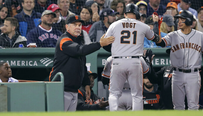 San Francisco Giants' Stephen Vogt (21) gets a pat on the back from manager Bruce Bochy, left, after his sacrifice that scored Kevin Pillar during the eighth inning of a baseball game against the Boston Red Sox at Fenway Park in Boston, Wednesday, Sept. 18, 2019. (AP Photo/Charles Krupa)