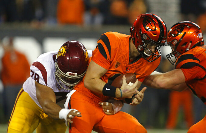 Oregon State quarterback Jake Luton, center, is sacked by Southern California's Jay Tufele, left, in the second half of an NCAA college football game in Corvallis, Ore., on Saturday, Nov. 3, 2018. Southern California won 38-21. (AP Photo/Timothy J. Gonzalez)