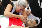 Lara, the wife of Alaa Abou Fakher who was killed by a Lebanese soldier on Tuesday night protests in southern Beirut, mourns over her husband's body during his funeral procession, in Choueifat neighborhood, Lebanon, Thursday, Nov. 14, 2019. For nearly a month, the popular protests engulfing Lebanon have been startlingly peaceful. But the death of the 38-year-old father by a soldier, the first such fatality in the unrest, points to the dangerous, dark turn the country could be heading into. (AP Photo/Hussein Malla)