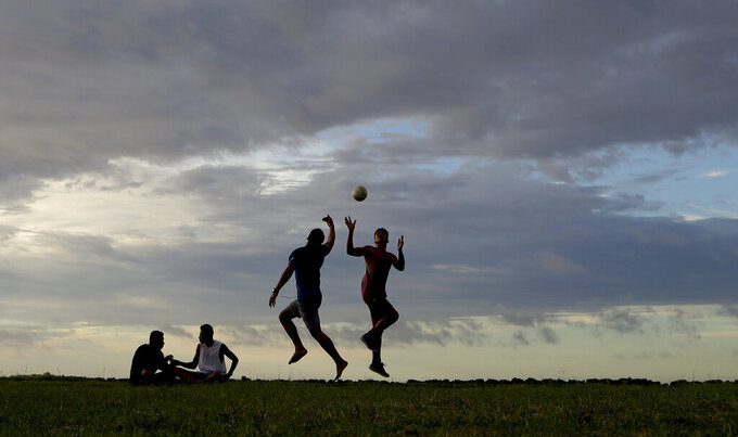 FILE - In this April 10, 2019, file photo, young men play a game of rugby at sunset in Nuku'alofa, Tonga. The largest cluster of places without the coronavirus can be found in the scattered islands of the South Pacific. Tonga, Kiribati, Samoa, Micronesia and Tuvalu are among those small nations yet to report a single case. But that doesn't mean they have been spared from the pandemic's effects. (AP Photo/Mark Baker, File)