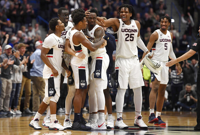 Connecticut players embrace teammate Sidney Wilson, center, after Wilson hit a three point basket to force over time in the second half of an NCAA college basketball game against Wichita State, Sunday, Jan. 12, 2020, in Hartford, Conn. (AP Photo/Jessica Hill)