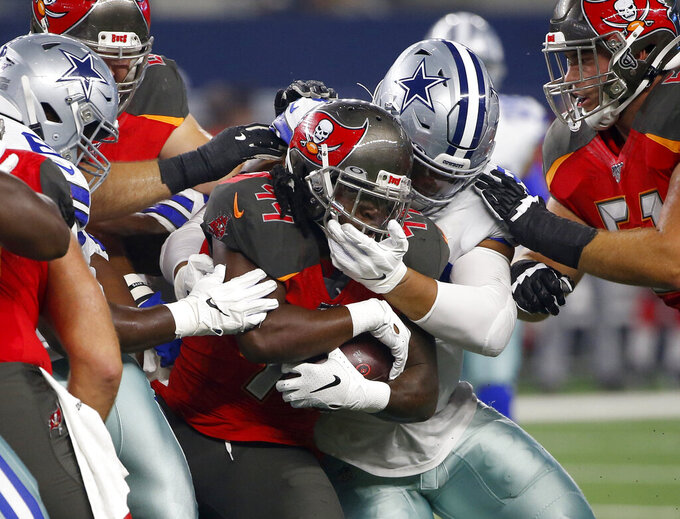 Tampa Bay Buccaneers running back Dare Ogunbowale, center left, is wrapped up on a run by Dallas Cowboys offensive guard Xavier Su'a-Filo, center right, in the first half of a preseason NFL football game in Arlington, Texas, Thursday, Aug. 29, 2019. (AP Photo/Ron Jenkins)