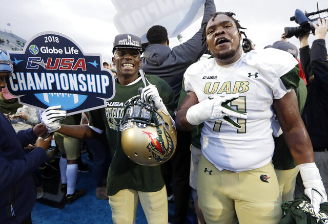 FILE - UAB players celebrate after defeating Middle Tennessee 27-25 in the Conference USA championship NCAA college football game Saturday, Dec. 1, 2018, in Murfreesboro, Tenn. Conference USA has schools stretching over 10 states, from Texas eastward and then toward the north. The 14-team league is within the footprint of the SEC, Big 12 and ACC. Like those Power Five leagues that play in the same region, C-USA is planning to be on the field this fall. (AP Photo/Mark Humphrey, File)