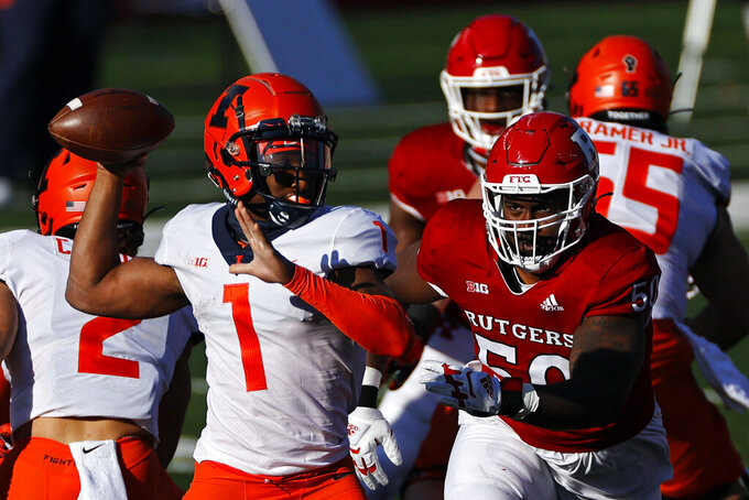 Illinois quarterback Isaiah Williams (1) passes under pressure from Rutgers defensive lineman Julius Turner during the first half of an NCAA college football game Saturday, Nov. 14, 2020, in Piscataway, N.J. (AP Photo/Adam Hunger)