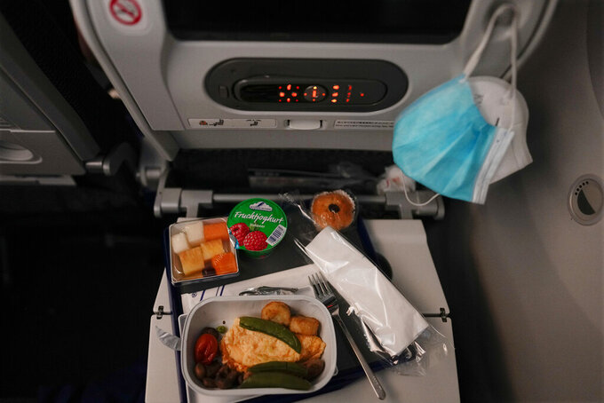 A breakfast sits in front of face masks on a tray table during a flight to Tokyo from Frankfurt, Germany, Monday, July 19, 2021. (AP Photo/Natacha Pisarenko)