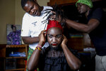 """In this photo taken Thursday, June 11, 2020, Raymond Brian, center, a Ugandan refugee and a nonconforming gender person who also goes by the name of """"Mother Nature"""" has makeup done by fellow Ugandan refugees Kasaali Brian, left, and Chris Wasswa, right, at a house that serves as a shelter for them in Nairobi, Kenya. """"People feel comfortable here because it's not far from the family setup,"""" Brian said. """"We use family therapy to help each other overcome the trauma from our pasts."""