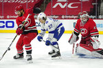 Carolina Hurricanes center Vincent Trocheck, left, reaches for the puck while Tampa Bay Lightning center Yanni Gourde (37) looks on in front of Hurricanes goaltender James Reimer (47) during the first period of an NHL hockey game in Raleigh, N.C., Monday, Feb. 22, 2021. (AP Photo/Gerry Broome)