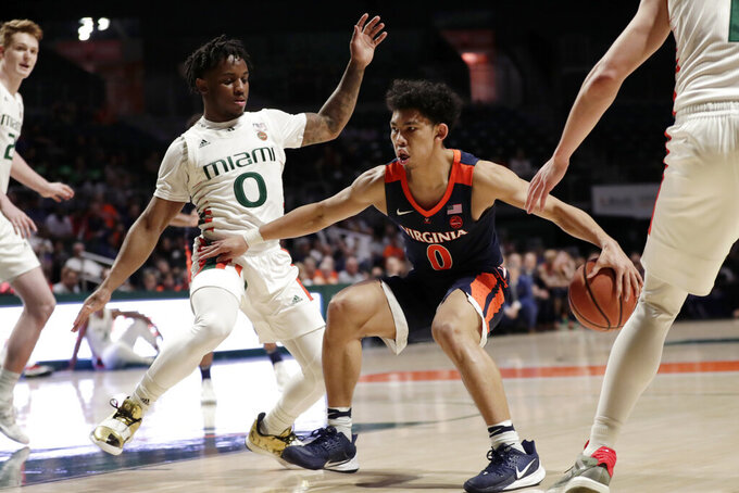 Virginia guard Kihei Clark, right, drives to the basket as Miami guard Chris Lykes (0) defends during the first half of an NCAA college basketball game, Wednesday, March 4, 2020, in Coral Gables, Fla. (AP Photo/Lynne Sladky)